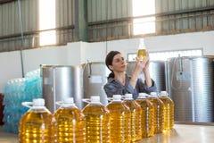Female technician examining olive oil Royalty Free Stock Photos
