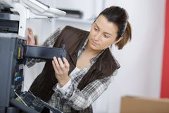 Female technician fixing photocopier machine. Female technician fixing a photocopier machine Stock Image