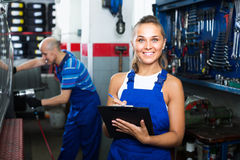 Female technician in overalls holding clipboard  in car workshop Royalty Free Stock Image