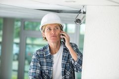 Female technician on phone fitting cctv camera Royalty Free Stock Image