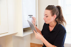 Female technician servicing boiler using tablet computer Stock Image