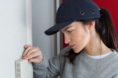 Female technician set thermostat at house. Female technician set the thermostat at house Stock Images