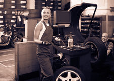 Female technician standing with wheel balancing machinery at aut Stock Photography