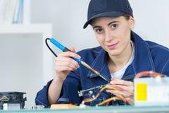 Female technician using soldering iron. Soldering Royalty Free Stock Image