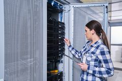 Female technician working on server maintenance. In white server room royalty free stock photo