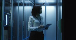 Female technician works on a tablet in a data center. Medium shot of female technician working on a tablet in a data center full of rack servers running stock images