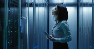 Female technician works on a tablet in a data center. Medium shot of female technician working on a tablet in a data center full of rack servers running royalty free stock photos