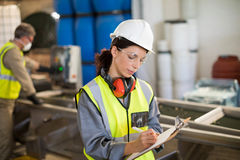 Female technician writing on clipboard Stock Photo