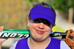 Female teen ballplayer. Head and shoulders portrait of a smiling teen girl in a baseball uniform, holding a bat horizontally against her back with a glove Stock Photo