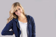Female teen with blond hair. Portrait of happy female teenager with long blond hair; studio background and copy space stock photos