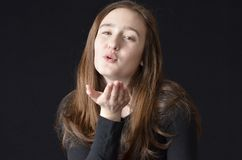 Blow me a kiss. Female teen blowing a kiss toward the camera Stock Photos