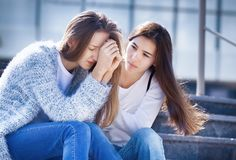 Teenager cries, her girlfriend sympathizes. The Female Teen is Crying because of Teenage Problems, and Her Friend Looks Sympathetically at Her, Sitting on the Stock Images
