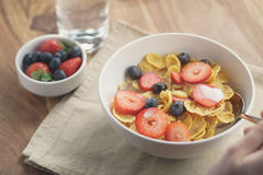 Female teen girl hand eats healthy breakfast with corn flakes and berries. Slightly toned photo Stock Image