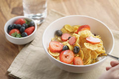 Female teen girl hand eats healthy breakfast with corn flakes and berries. Slightly toned photo Stock Photography