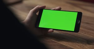 Female teen girl hold smartphone with green screen over wood table Stock Photos