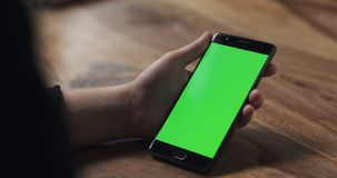 Female teen girl hold smartphone with green screen over wood table Royalty Free Stock Images