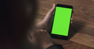 Female teen girl hold smartphone with green screen over wood table Stock Image