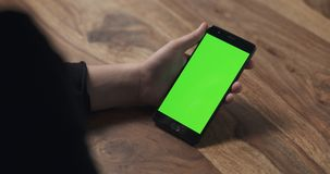 Female teen girl hold smartphone with green screen over wood table Royalty Free Stock Photography