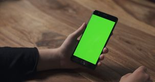 Female teen girl hold smartphone with green screen over wood table Royalty Free Stock Image