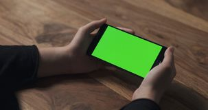 Female teen girl hold smartphone with green screen over wood table Royalty Free Stock Photo
