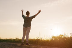 Female teen girl stand feel freedom with arms stretched to the sky copy space for your info Royalty Free Stock Images