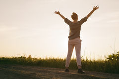 Female teen girl stand feel freedom with arms stretched to the sky copy space for your info Royalty Free Stock Photo