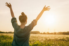 Female teen girl stand feel freedom with arms stretched to the sky stock image