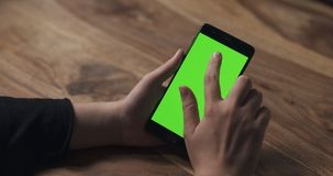 Female teen girl using smartphone with green screen over wood table Stock Photo