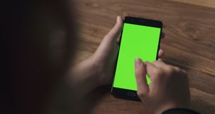 Female teen girl using smartphone with green screen over wood table Royalty Free Stock Photos