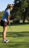 Female teen golfer putting on green Stock Photo