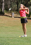 Female teen golfer teeing off Stock Image