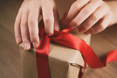 Female teen hand going to untie bow on gift box Royalty Free Stock Images