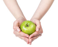 Female teen hands holding green apple Royalty Free Stock Photo