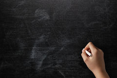 Female teen hand to draw something on blackboard. With chalk Royalty Free Stock Photos