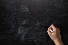 Female teen hand to draw something on blackboard Royalty Free Stock Photos