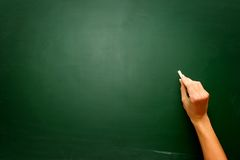 Female teen hand to draw something on blackboard with chalk. Concept Royalty Free Stock Photos