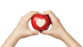 Female teen hands holding apple with carved heart. Isolated on white royalty free stock photography