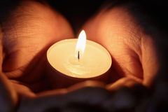 Female teen hands holding burning candle Stock Photos