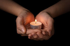 Female teen hands holding burning candle. In the dark Stock Image