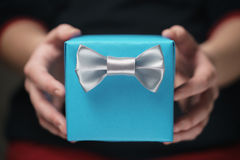 Female teen hands show blue paper gift box with gentleman bow Royalty Free Stock Photography