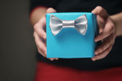 Female teen hands show blue paper gift box with gentleman bow Royalty Free Stock Images