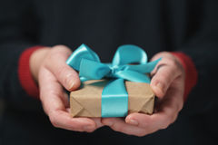 Female teen hands show craft paper gift box with blue bow Stock Images