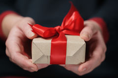 Female teen hands show craft paper gift box with red bow Royalty Free Stock Photos