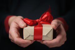Female teen hands show craft paper gift box with red bow Stock Images