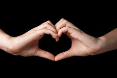 Female teen hands showing heart symbol. Isolated on black Stock Image