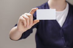 Female teen holding empty business card in front of camera Royalty Free Stock Image