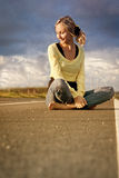Female teen sits. In the middle of the highway.  She is uncertain of her future and struggling with decisions Royalty Free Stock Images