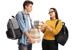Female teen student giving a stack of books to a male teen stude. Nt isolated on white background Royalty Free Stock Photos