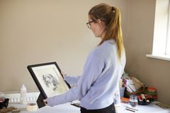 Female Teenage Artist Holding Framed Charcoal Drawing Of Dog In Studio royalty free stock images