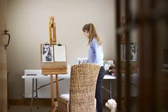 Female Teenage Artist Preparing To Draw Picture Of Dog From Photograph royalty free stock image